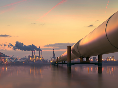 Oil pipeline in industrial district with factories at dusk 517340891