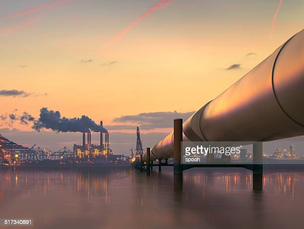 oil pipeline in industrial district with factories at dusk - pollution stock pictures, royalty-free photos & images