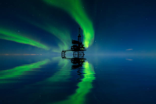 Oil platform at sea at the northern lights background. Oil production in the north