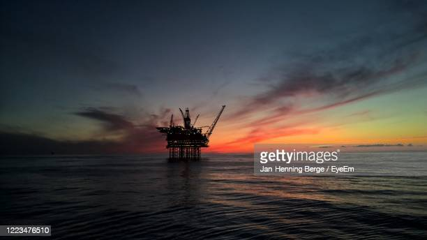 oil plattform inn the nothsea  inn calm sea against sky during sunset - norway stock pictures, royalty-free photos & images