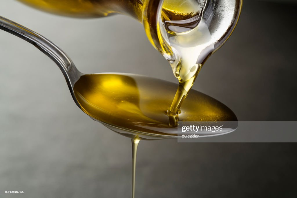 Oil pouring and dripping to the spoon : Stock Photo
