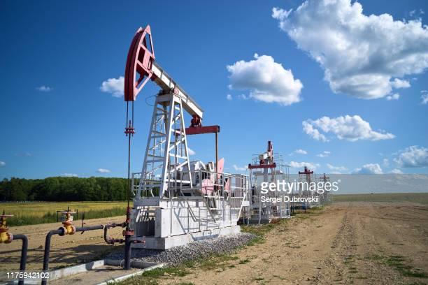 pompa dell'olio, campo, cielo nuvoloso blu - russia foto e immagini stock