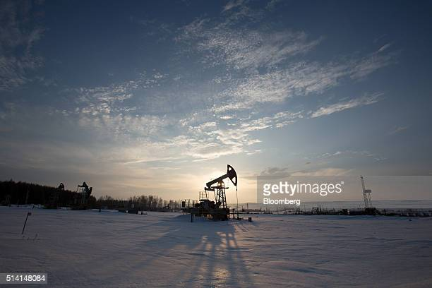 A oil pumping jack also known as a 'nodding donkey' operates in a snow covered oilfield near a derrick right during drilling operations in an...