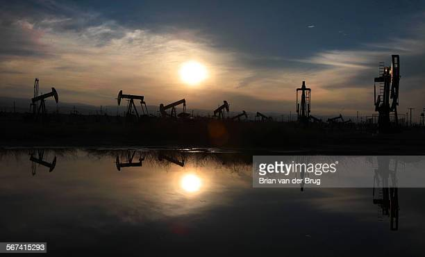 Oil pumps and equipment reflect on water pooled after recent storm in the South Belridge oil field in Kern County March 4, 2014 about forty miles...