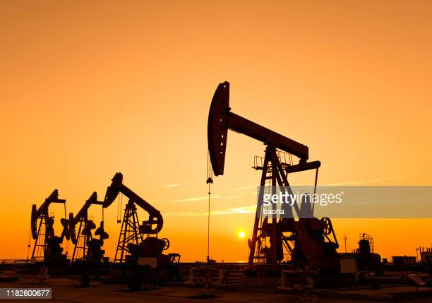 oil pumps and rig at sunset - gasoline stock pictures, royalty-free photos & images