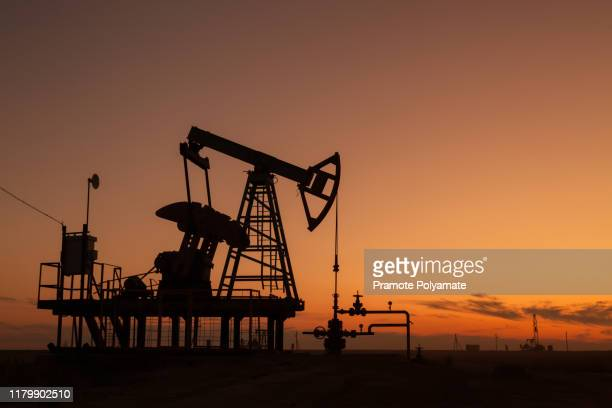oil pumps at sunset,  industrial oil pumps equipment. - oil stock pictures, royalty-free photos & images