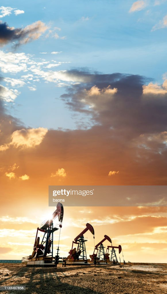 Oil pumps working under the sunrise sky : Stock Photo