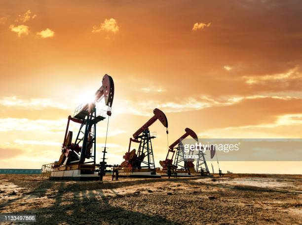 oil pumps working under the sunrise sky - oil field stock pictures, royalty-free photos & images
