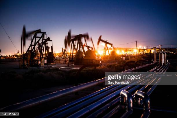 oil pupjacks whiring at night - oil stock pictures, royalty-free photos & images