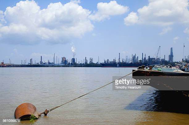 oil refineries on river with bow of moored barge - timothy hearsum stock photos and pictures