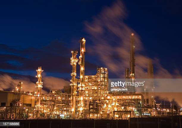 oil refinery illuminated at night - petrochemical plant stock pictures, royalty-free photos & images