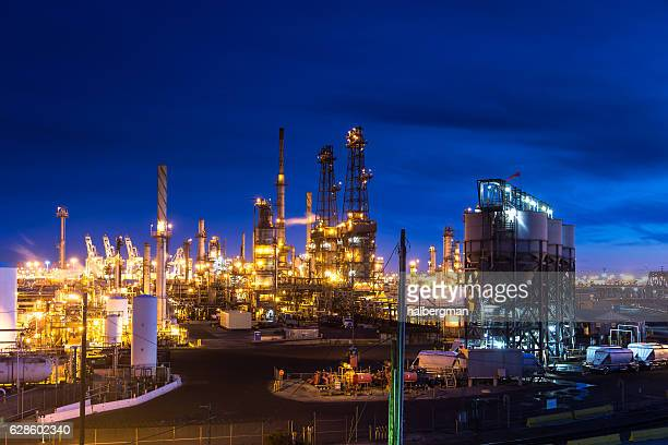 oil refinery lit up at night - flare stack stock photos and pictures