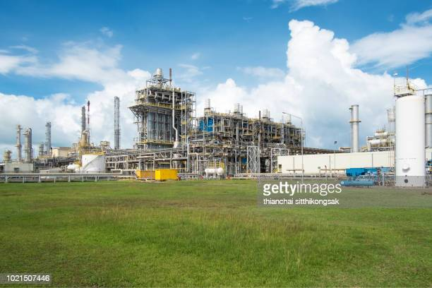 Oil refinery plant on grass field and clear sky