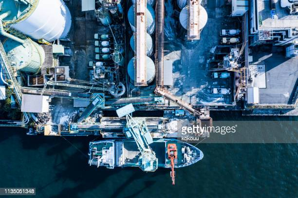 oil refinery storage units with tanker ships - storage compartment stock pictures, royalty-free photos & images