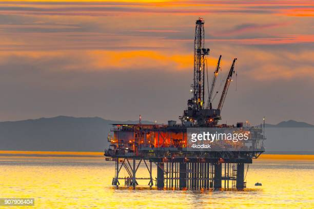 oil rig and surfer off the huntington beach in california - drill stock pictures, royalty-free photos & images