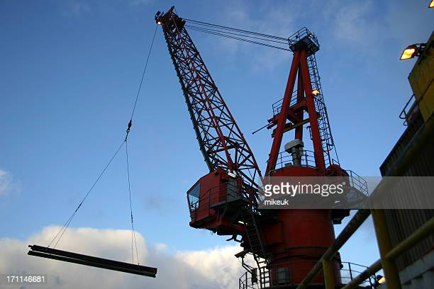 oil rig crane lifting drill pipe from a boat