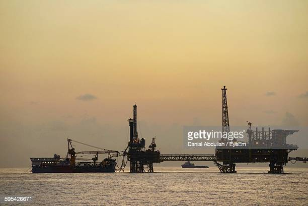 Oil Rig In Sea Against Sunset Sky