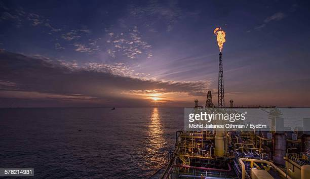 oil rig over sea against sunset sky - industrial sailing craft stock pictures, royalty-free photos & images