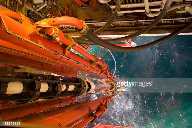 oil rig view riser pipes down to sea level - north sea stock pictures, royalty-free photos & images