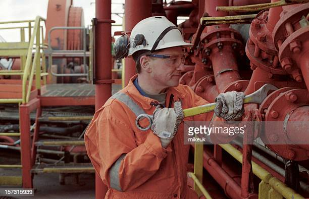Oil rig worker fixing the pipes