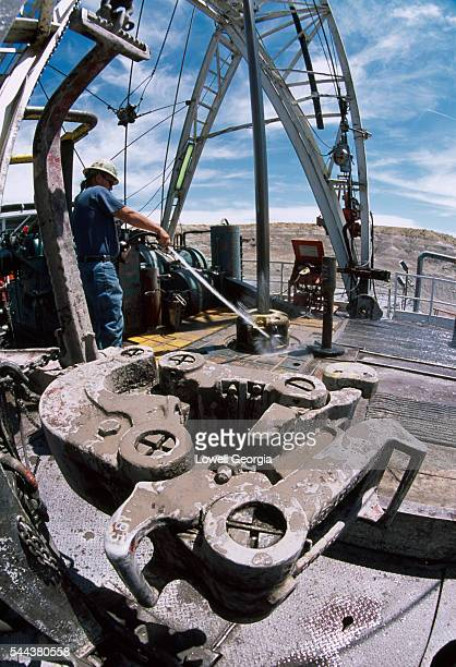 Oil Rig Worker Washing Rig Floor and Power Tongs