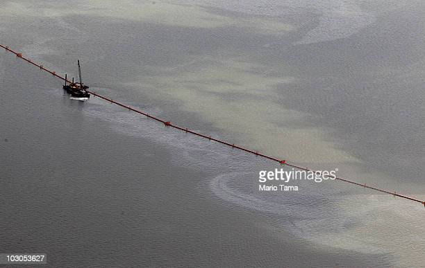 Oil sheen and boom are seen July 23 2010 in Grand Isle Louisiana Ships and rig workers are evacuating the oil spill area as Tropical Storm Bonnie...