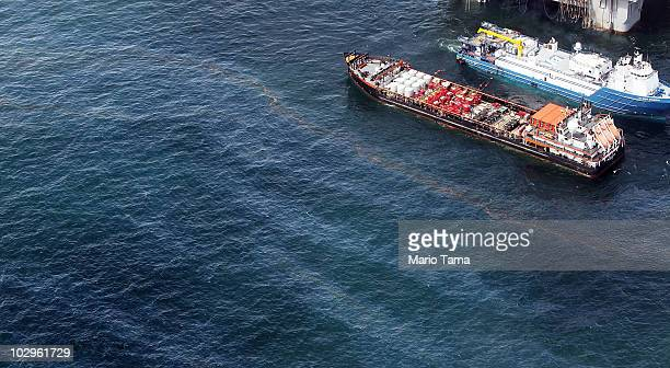 Oil sheen is seen with vessels assisting near the source of the BP Deepwater Horizon oil spill on July 18 2010 in the Gulf of Mexico off the coast of...