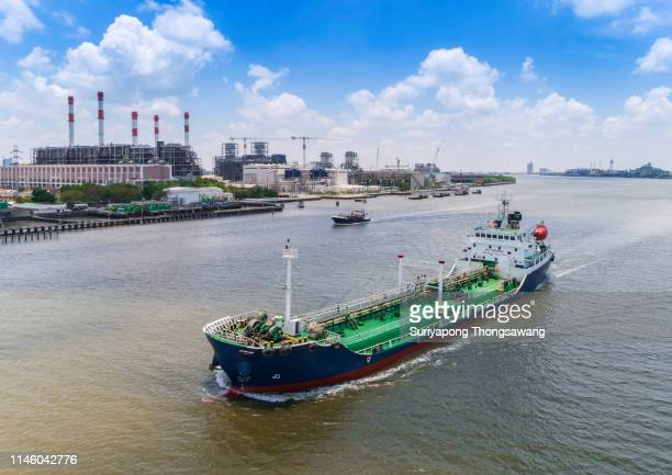 oil ship tanker in river transportation oil from refinery. - motor oil stock pictures, royalty-free photos & images