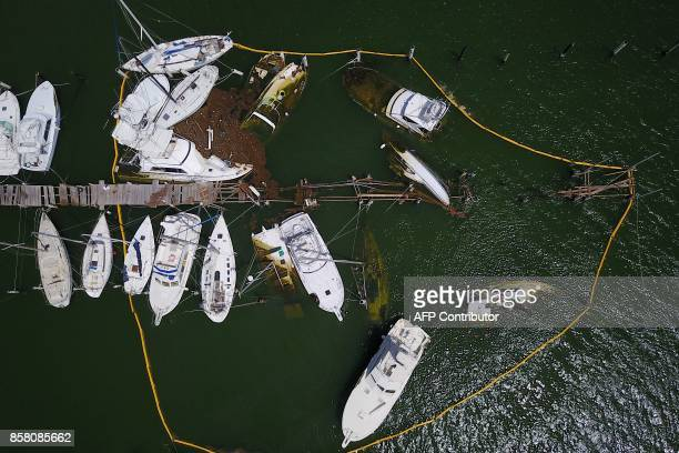 TOPSHOT Oil spill containment barriers surround sunk and damaged boats affected by the passing of Hurricane Maria in Fajardo Puerto Rico on October 4...