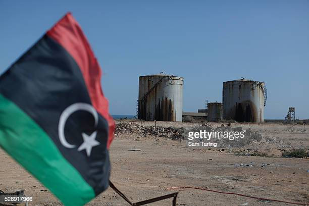 Oil storage containers that appear to have been perforated by gunfire stand abandoned by a checkpoint manned by forces loyal to the 'Libyan Dawn'...