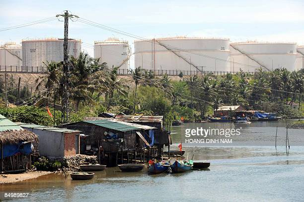 Oil storage tanks from Vietnam's first oil refinery at Dung Quat loom over poor shanty homes along the water on February 22, 2009 in the central...