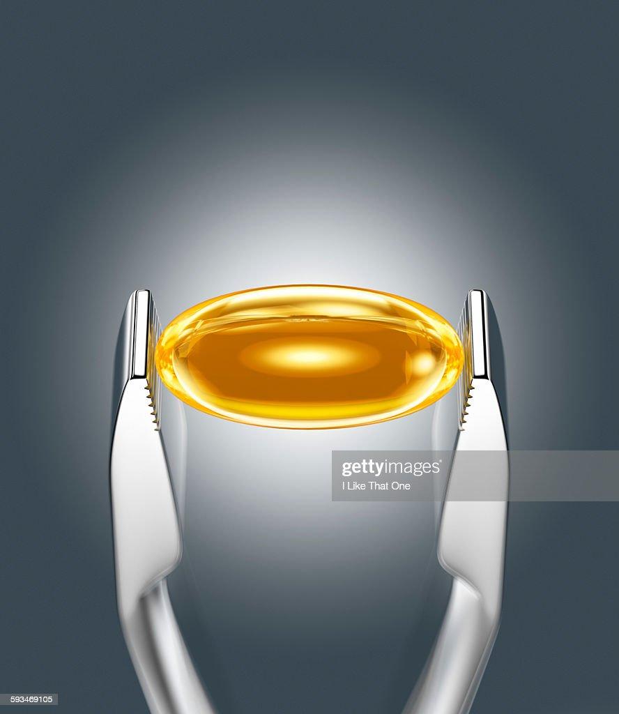 Oil supplement held between pincer : Stock Photo