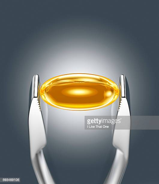 oil supplement held between pincer - atomic imagery stock pictures, royalty-free photos & images