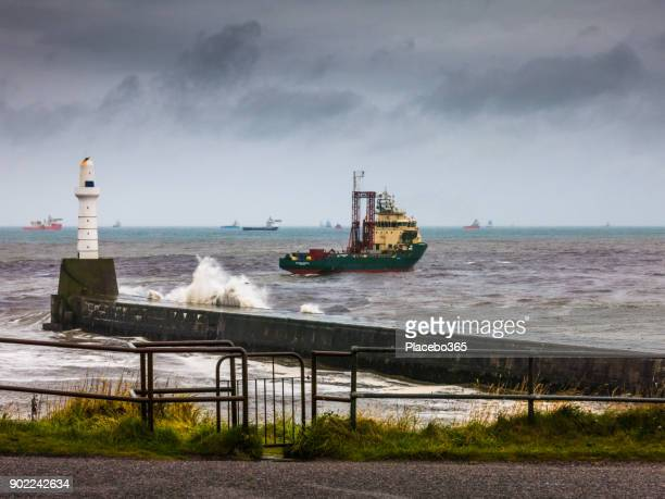 oil supply boat leaving harbour during storm in north sea, aberdeen, uk - retaining wall stock pictures, royalty-free photos & images