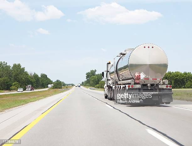 Oil tanker semi truck driving down highway
