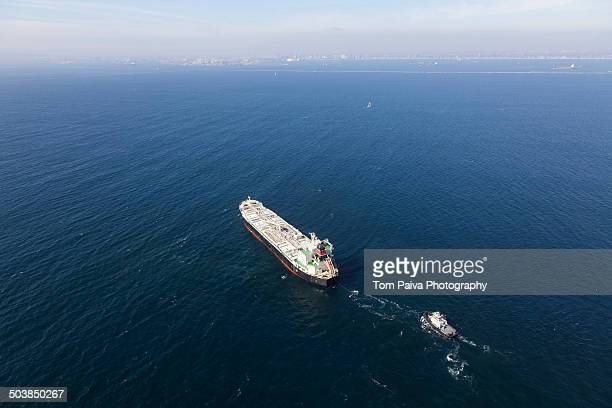 Oil tanker with tugboat at sea