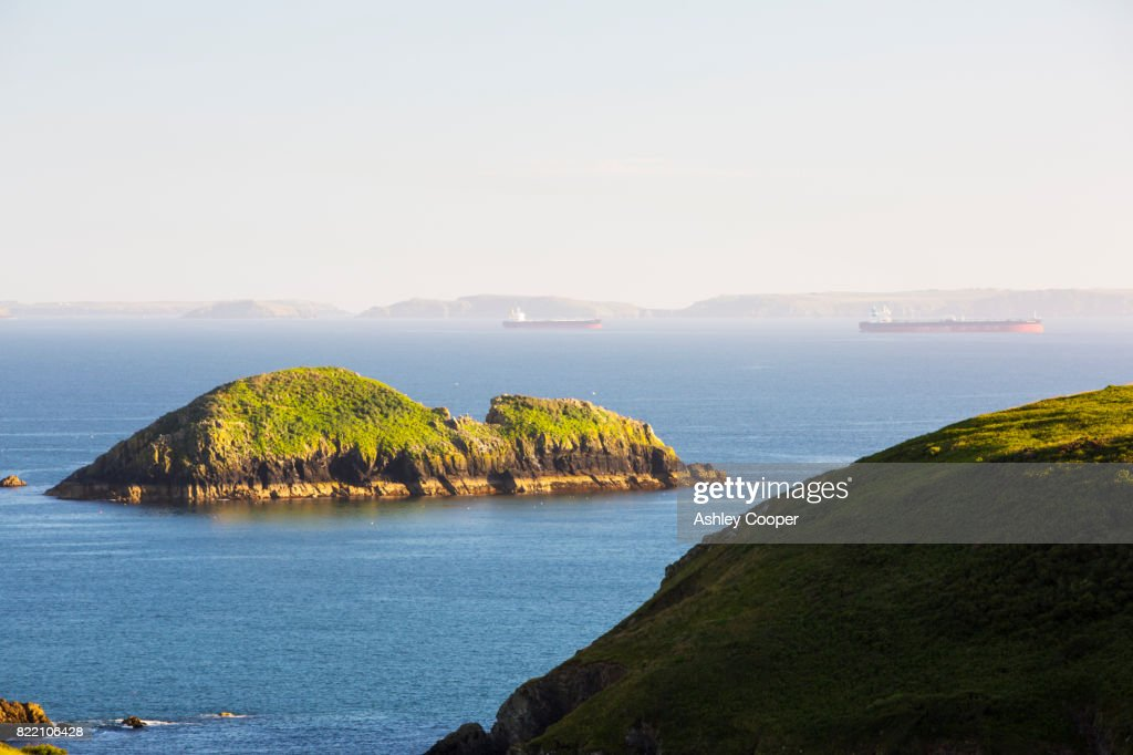Oil tankers moored in St Brides Bay from Solva in Pembrokeshire, Wales, UK, with Green Scar island in the foreground. : Stock Photo