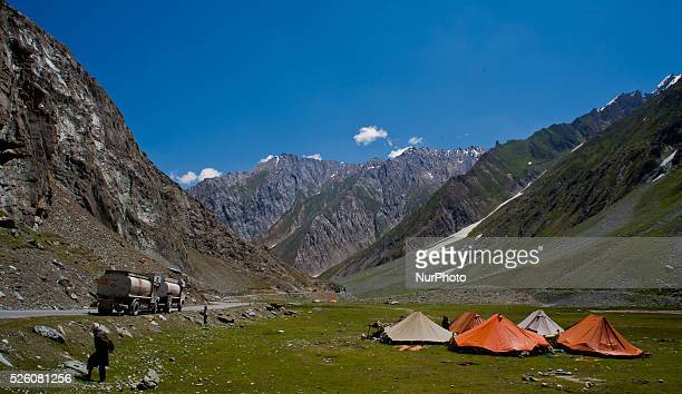 Oil tankers pass on a highway next to the tents erected by Muslim nomads on July 30 2015 in Drass 142 km east of Srinagar the summer capital of...
