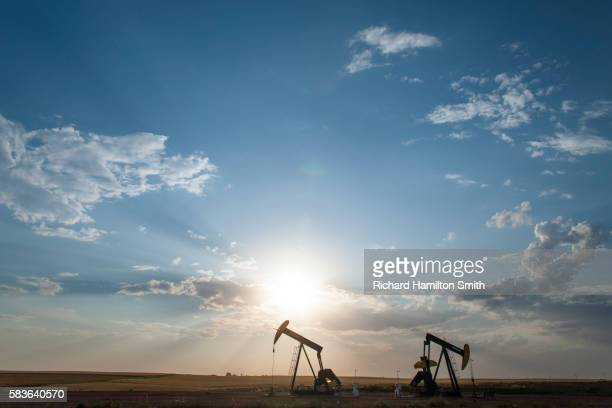 oil wells in wheat field - north dakota stock pictures, royalty-free photos & images