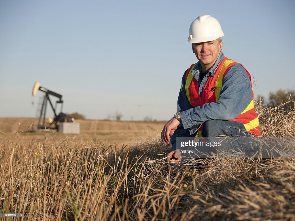Oil Worker in Safety Gear at Well Pumpjack : Stock Photo