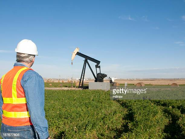 Oil Worker in Safety Gear at Well Pumpjack Site