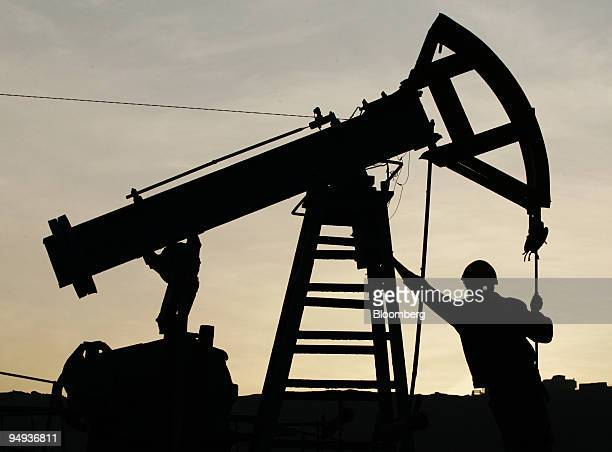 A oil worker works on a oil pump