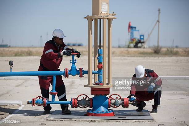 Oil workers adjust flow valves on a modern oil pumping unit at an oilfield operated by Embamunaigas a unit of KazMunaiGas Exploration Production in...