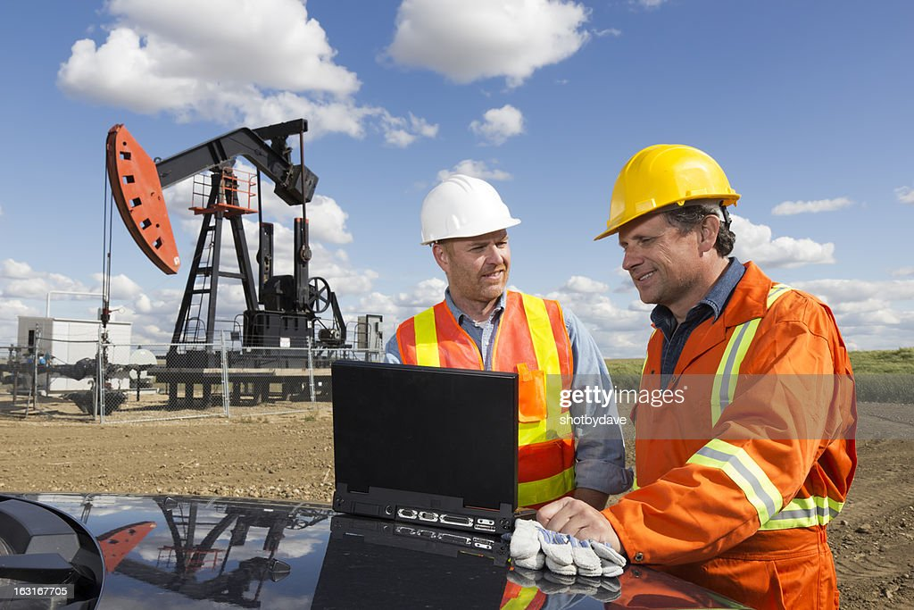 Oil Workers and Laptop : Stock Photo