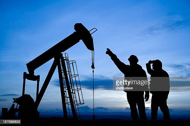 Oil Workers Inspecting a Pump Jack