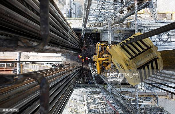 Oil workers operate drill sections while working on the drilling floor beneath the travelling block right on a derrick operated by Salym Petroleum in...