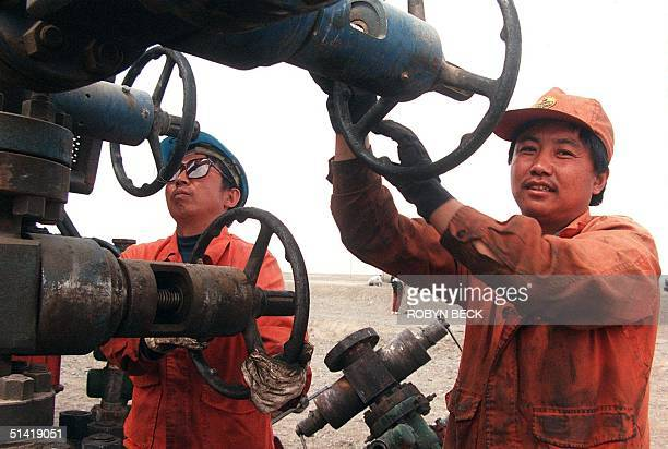 Oil workers release values to pump high pressure water into the underground oil field to force the oil out of the ground at a well on the Tuha...
