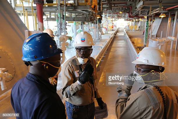 Oil workers stand on top of a newly restored oil storage tank aboard the Agbami floating production storage and offloading vessel operated by Chevron...