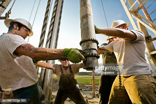 oil workers using chain to position drill on drilling platform - drill stock pictures, royalty-free photos & images