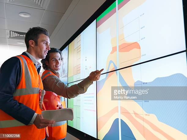 oil workers with geology screen - geologi bildbanksfoton och bilder
